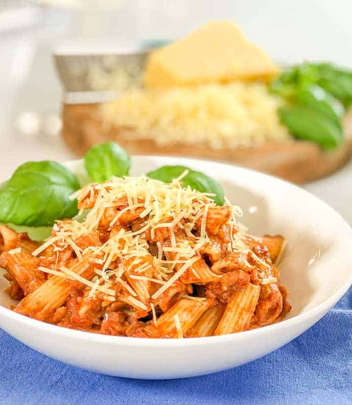 Bowl of tomato bacon pasta sauce with penne pasta and shredded cheese.