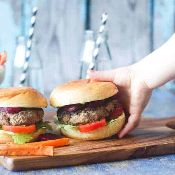 Tray of beef burgers with lettuce, tomato and beetroot.