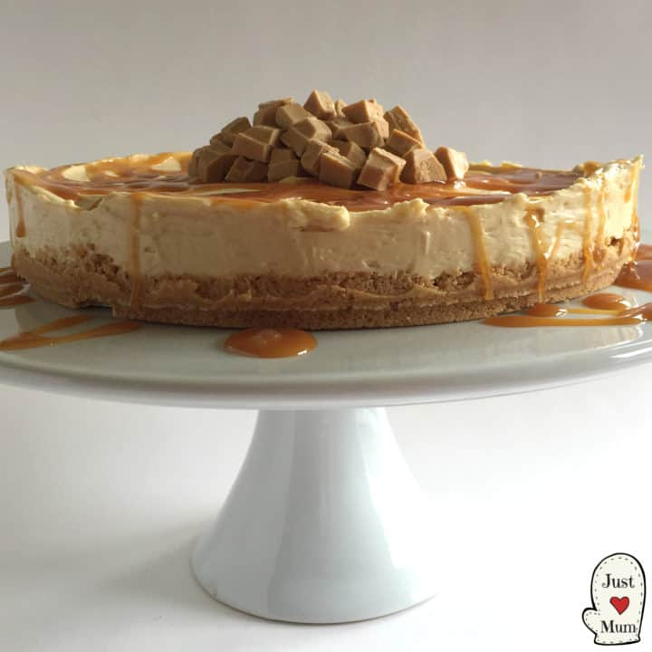 Caramilk Cheesecake with dripping topping all over sits on a cake stand.