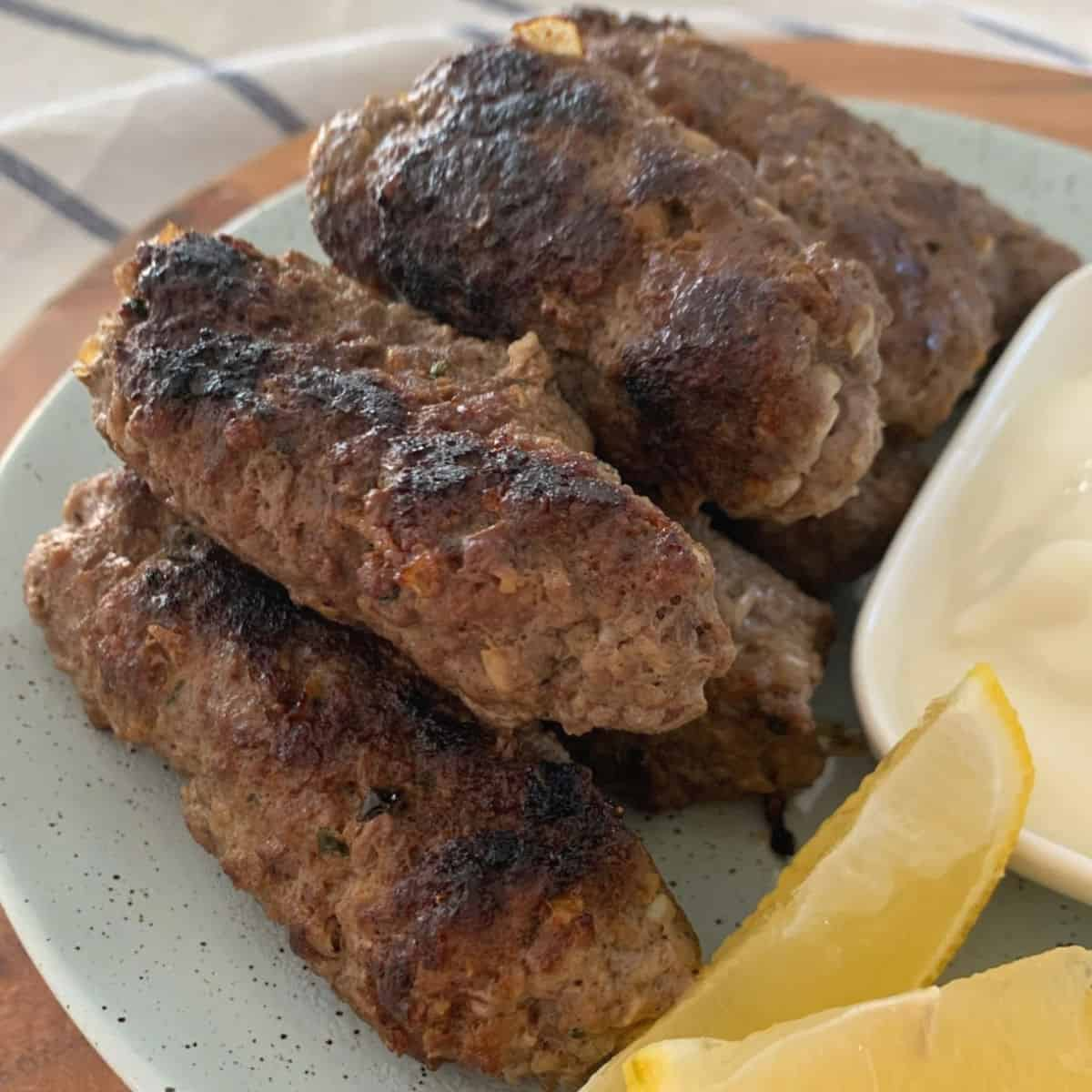 Side view of beef koftas on a plate with lemon