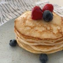 Stack of pancakes topped with berries