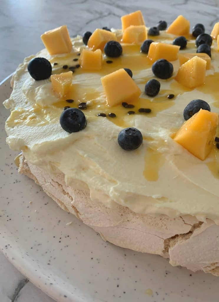 Pavlova topped with mango, passionfruit and blueberries