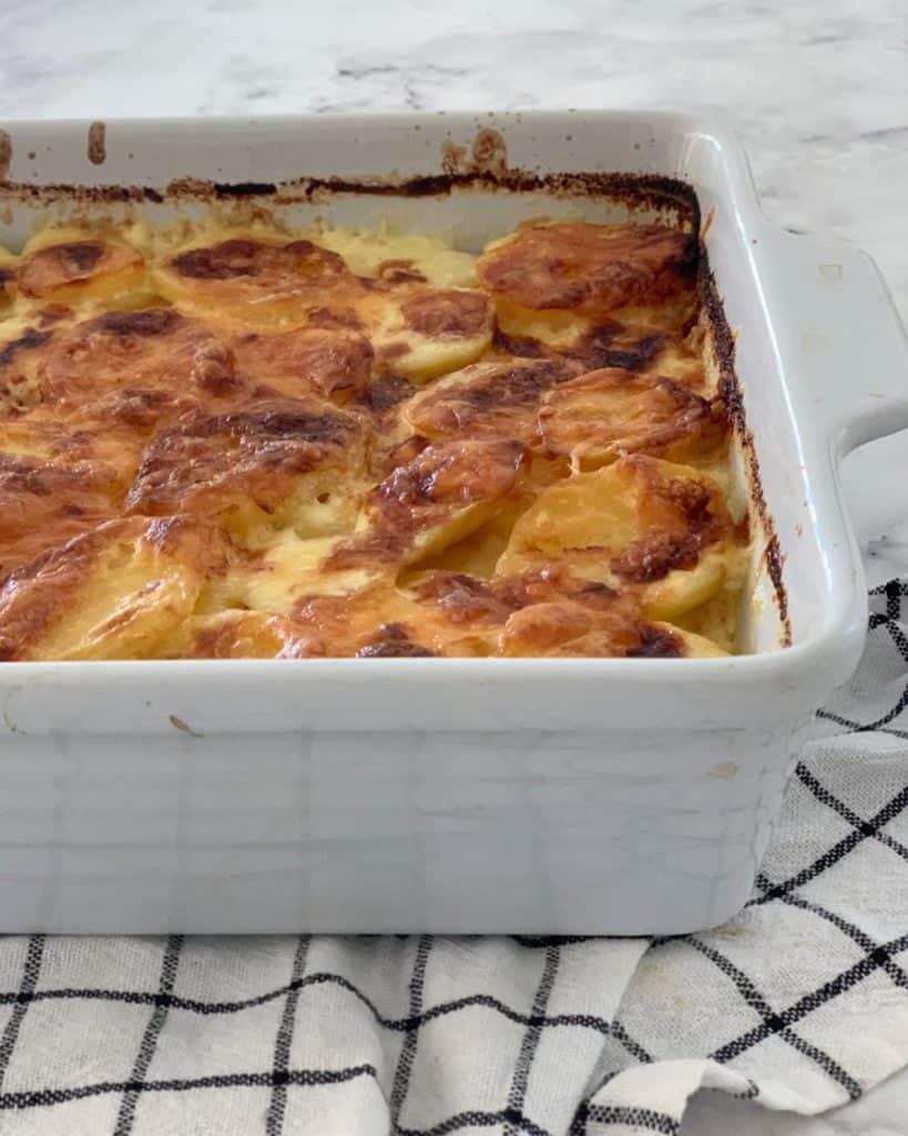 Cheesy Potato Bake in a white dish on towel.