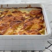 Cheesy Potato Bake in a white dish on towel.