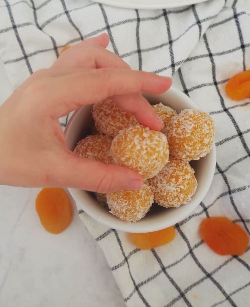 Child's hand reaching for apricot bliss ball