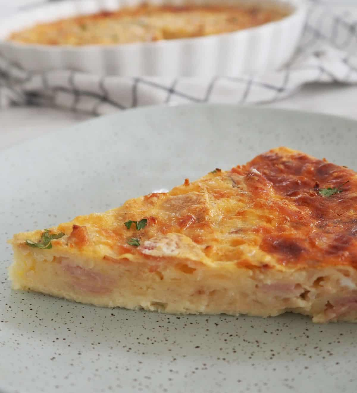 Slice of egg and bacon pie on a green plate