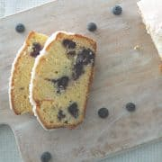overhead view of sliced lemon and blueberry loaf on timber board