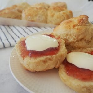 Lemonade Scones on a plate with strawberry jam and cream