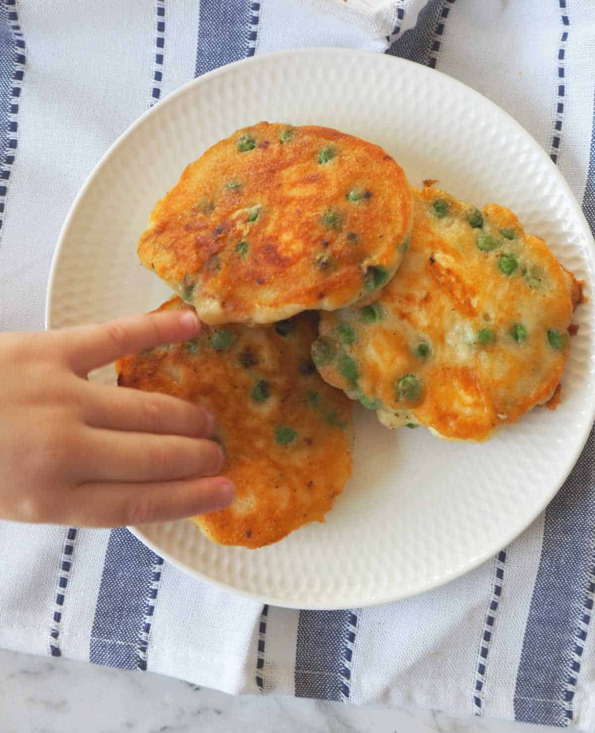 Child reaching for a pea fritter on a white plate