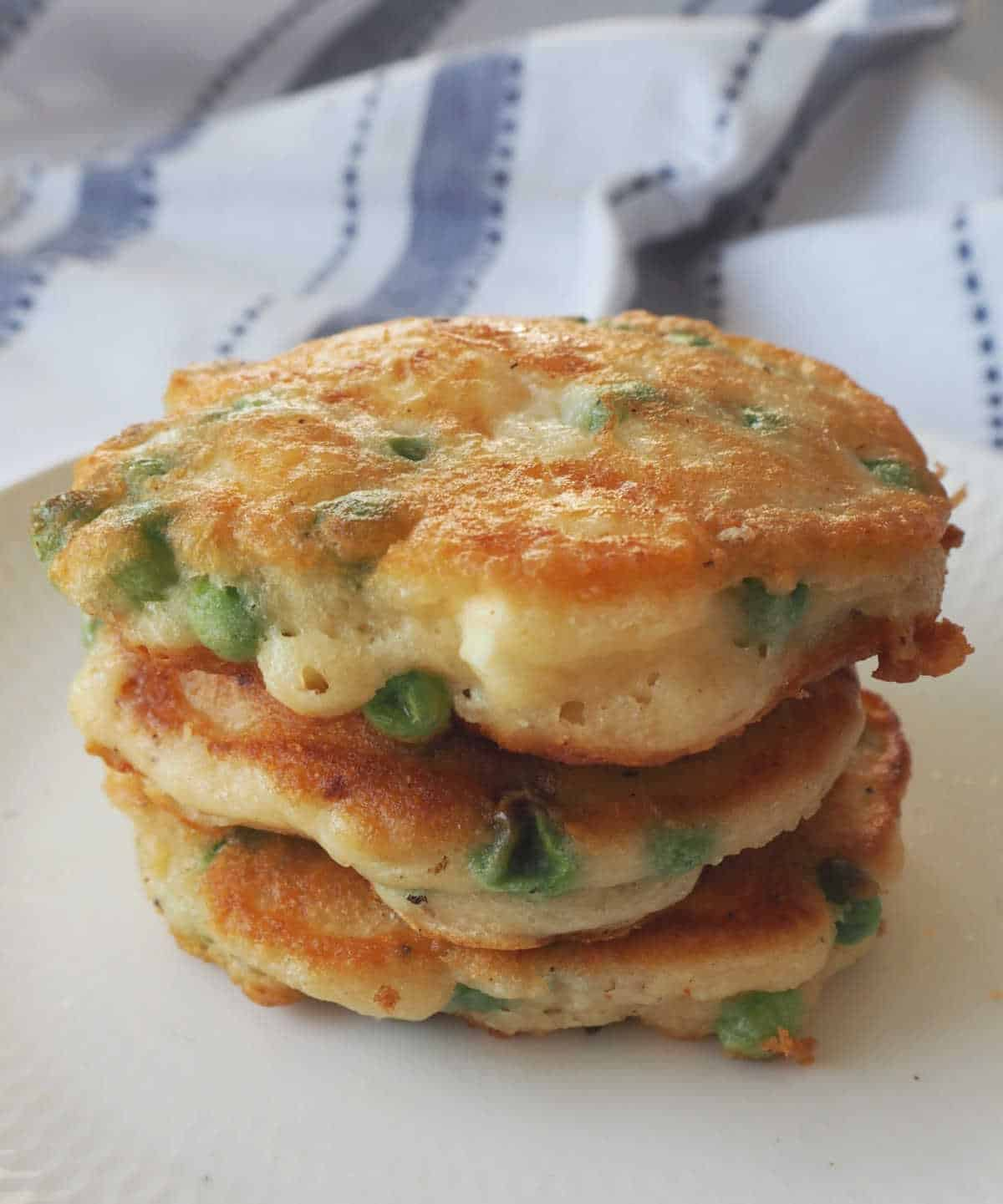 Pea Fritters stacked on a white plate