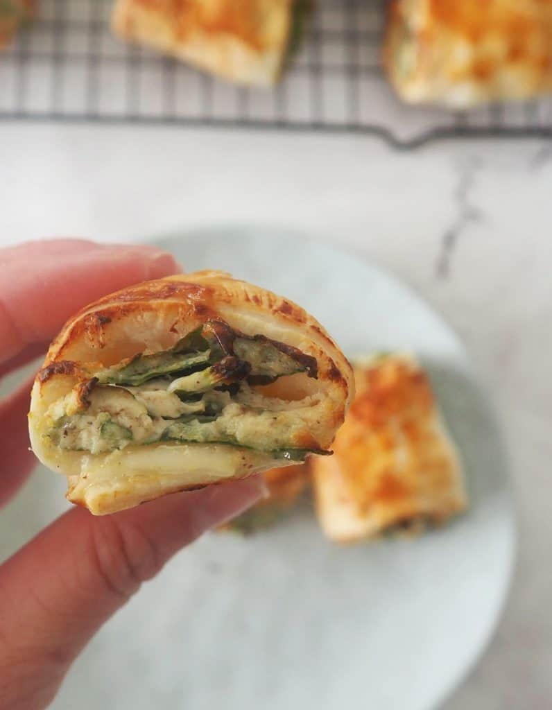 Adult holding a spinach and ricotta roll showing the side view