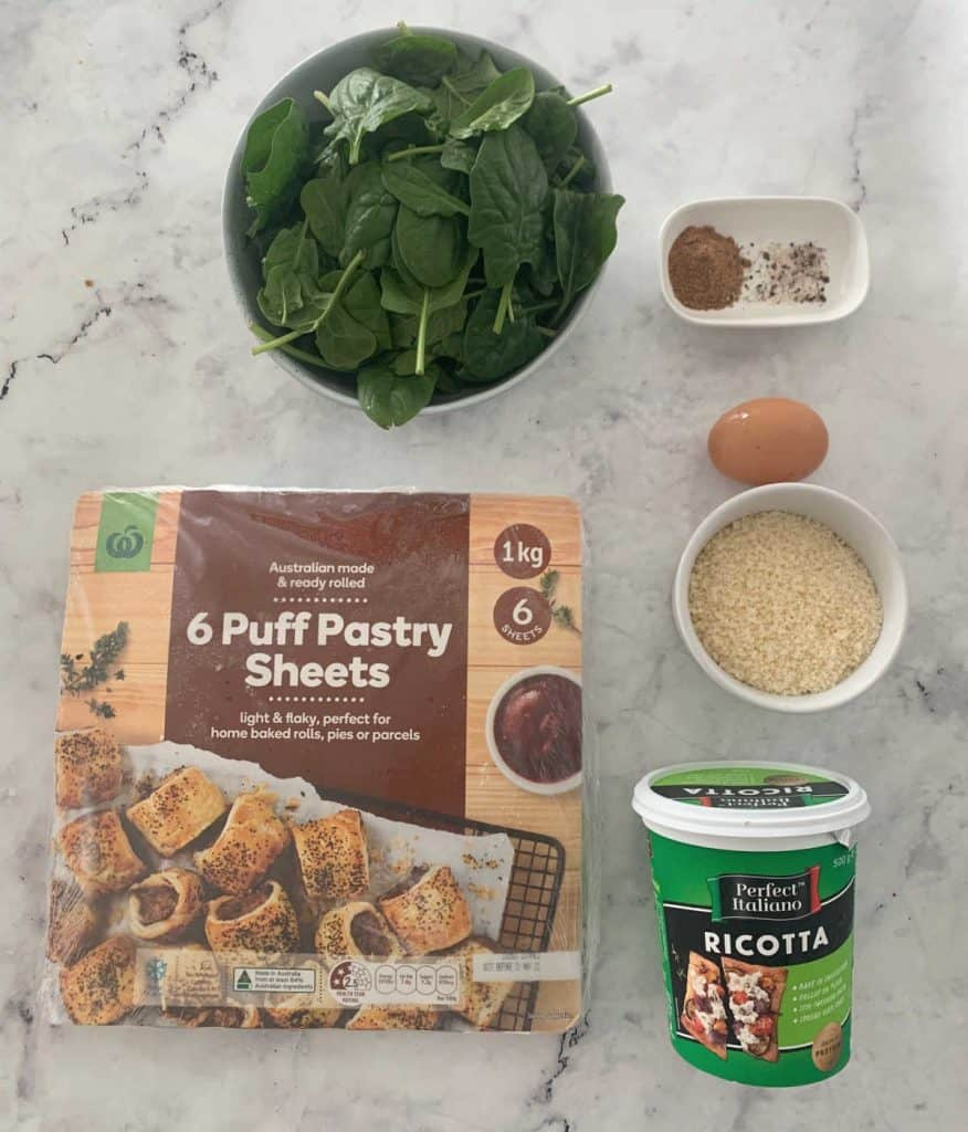 Ingredients to make spinach and ricotta rolls placed on a marble surface