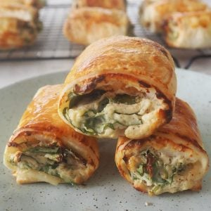 Close up of three spinach and ricotta rolls stacked on a green plate.
