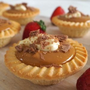 side view of caramel tarts on a wooden board