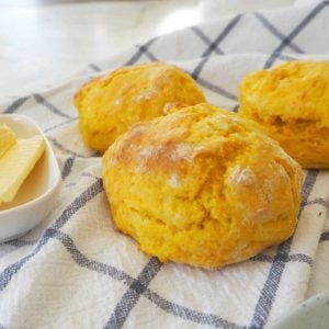 close up side view of pumpkin scones on a blue and white checkered tea towel