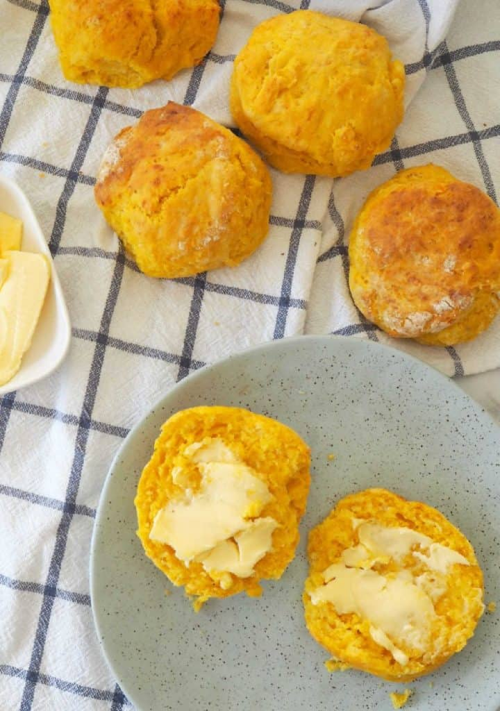 Overhead view on pumpkin scones buttered on a green plate