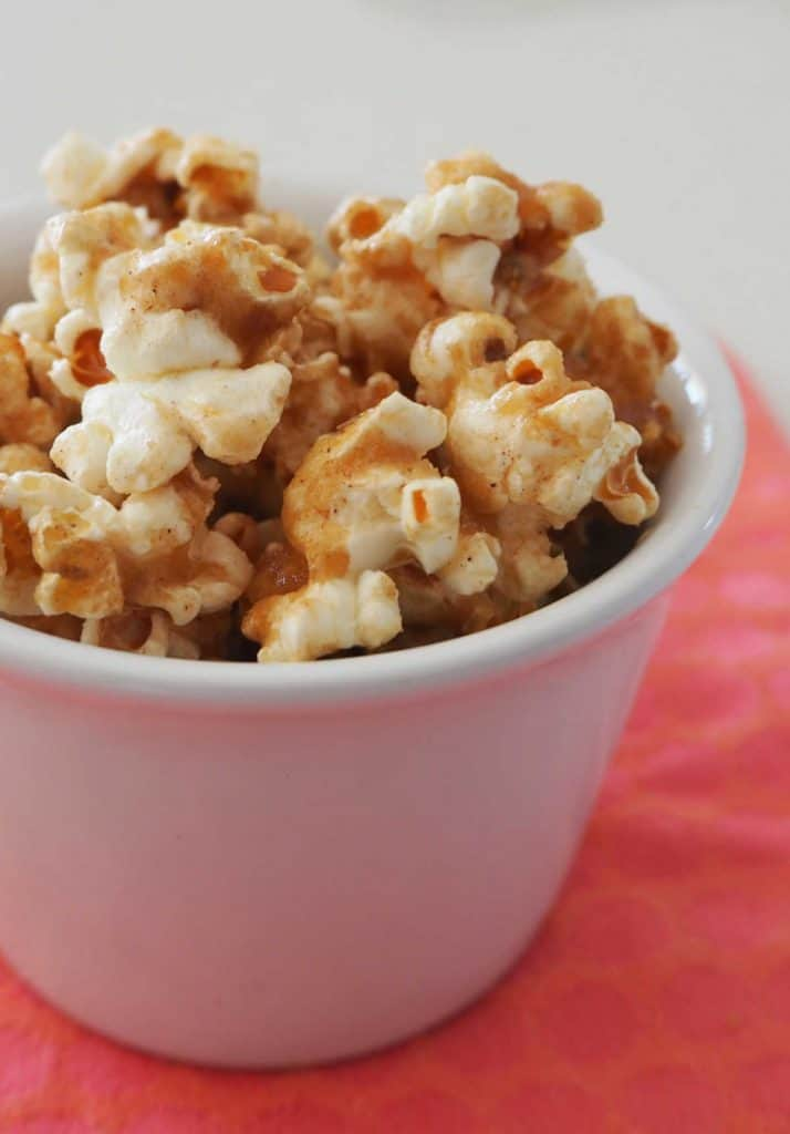 Cinnamon popcorn in a white bowl on a pink background