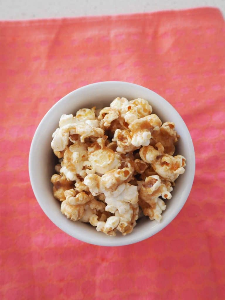 overhead view of Cinnamon popcorn in a white bowl on a pink background