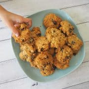 a child's hand reaching for an oatmeal raisin cookie