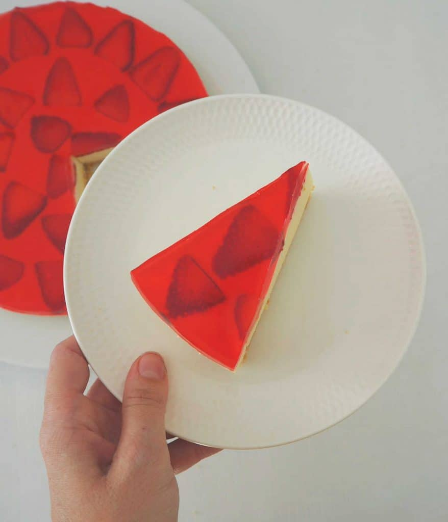 overhead view of a piece of Strawberry Jelly Cheesecake on a white plate being held